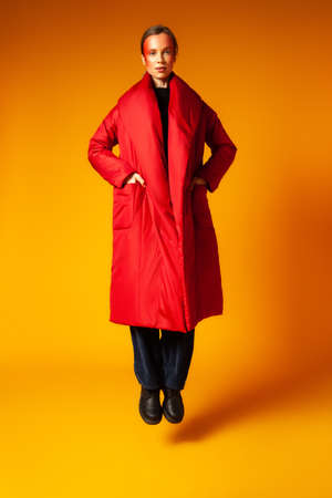 Trendy female in oversize coat jumping against yellow background