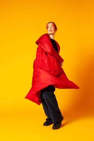 Female model in baggy coat spinning around against yellow background Standard-Bild