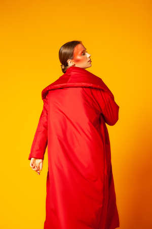Female model in bright red coat against yellow background