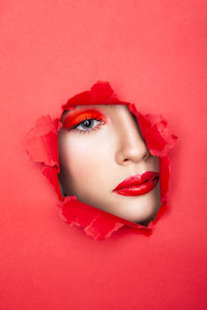 Woman with red visage looking through torn paper