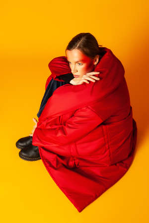 Lonely woman wrapping in baggy coat against yellow background
