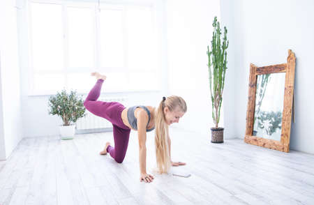 Slim sportswoman exercising in cozy room at home