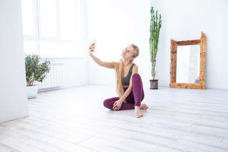 Female athlete taking selfie against mirror and plant