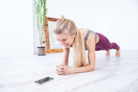 Cheerful sportswoman doing plank exercise near smartphone Standard-Bild