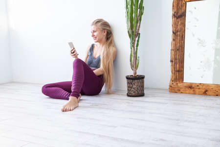 Sportswoman browsing smartphone near plant and mirror