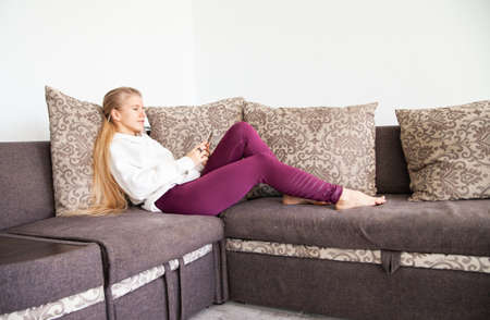 Young woman browsing smartphone on sofa at home
