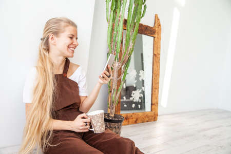 Cheerful young woman with mug using smartphone Standard-Bild