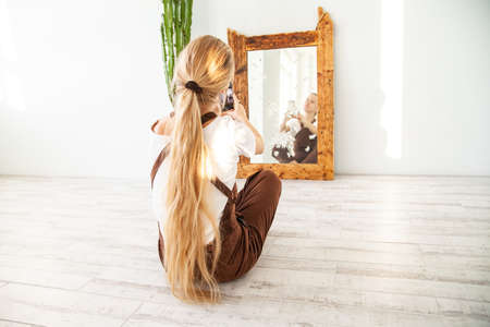 Young female taking selfie in front of mirror