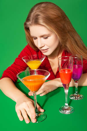 Young female with colorful alcohol drinks on green background
