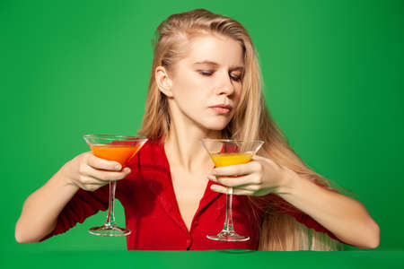 Young woman choosing between cocktails on green background