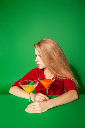 Young woman resting near colorful cocktails on green background