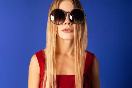 Young woman in trendy sunglasses on blue background