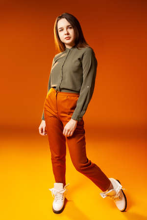Trendy young woman looking at camera against orange background