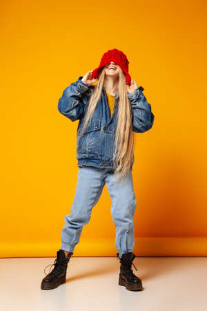 Cheerful trendy woman in denim outfit and hat having fun in studio