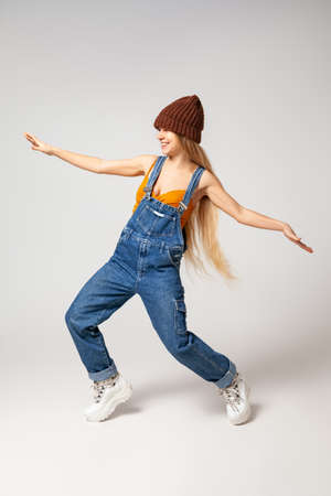 Stylish hipster woman dancing in studio against white background