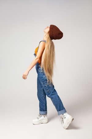 Energetic hipster woman in trendy wear dancing in studio