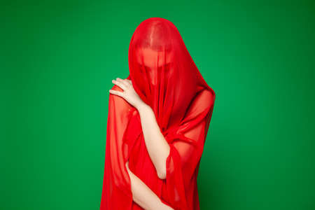 Dreamy woman under red veil against green background