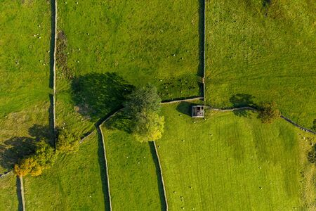 An aerial shot of a derelict barn light by spring sunshine