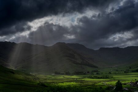 Stormy skies and a bright sun trace light over The Langdale Pikes in the English Lake District Stock Photo