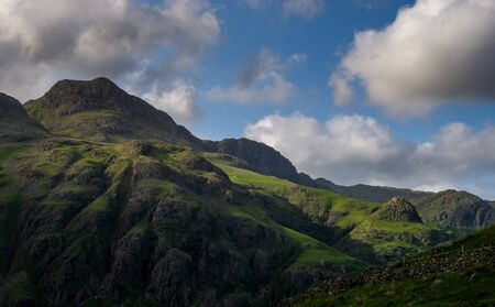 Stormy skies and a bright sun trace light over The Langdale Pikes in the English Lake District