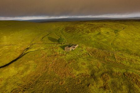 An aerial Sunrise drone shot of Top Withens or Top Withins, this farmhouse has been associated with
