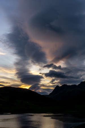 Blea Tarn and The Langdales are silhouetted by cloud formations during sunset in the English Lake District