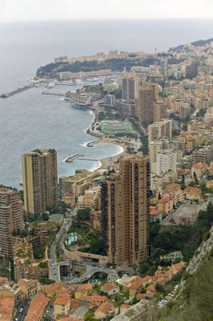 Nice view from a hill over the coastal line of Monaco with its marina and luxury towers. In the background on the peninsula, the palace of the Grimaldi .