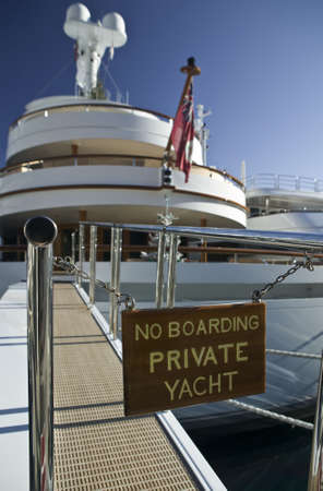 Luxury yacht with footbridge, prohibition sign and white  tree.
