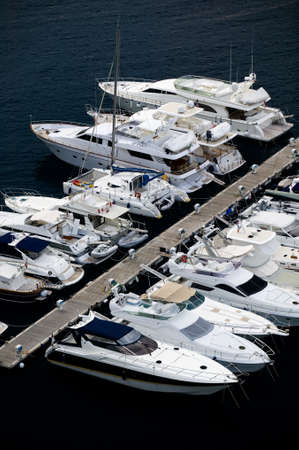 Luxury yachts at a wooden pier in Monte Carlo, Monaco.