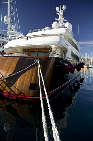 Detail shot of a nice wooden luxury yacht, locked with big cords at harbor of Monaco.