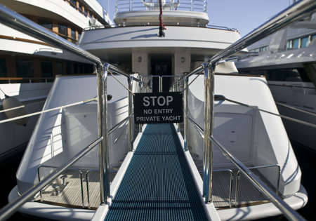 Rear of a luxury yacht with footbridge, reling and prohibition sign. Stock Photo