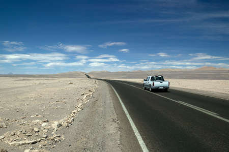 Nice modern Pick-up truck, underway on a straight highway through the Atacama Desert, Chile.