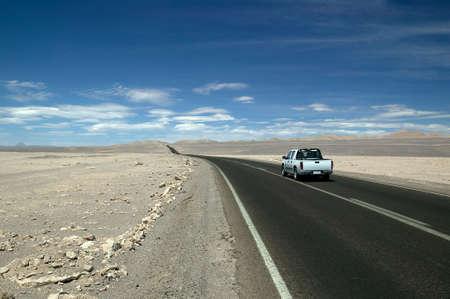 Nice modern Pick-up truck, underway on a straight highway through the Atacama Desert, Chile.