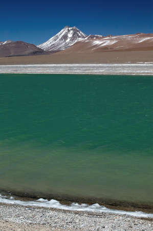 Snowcapped volcano with a ice crusted, cold green mountain lake, located in the Argentinean highlands. Stock Photo - 2874936