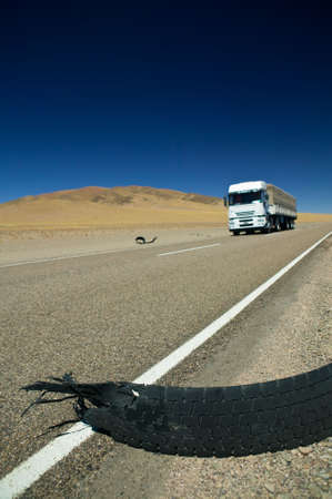 White truck crossing a destroyed tire in a desert. photo