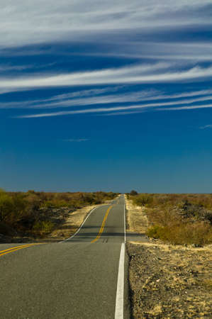 Perspectiv view of a straight highway with a lot of bumps and a deep blue sky. Stock Photo - 2874883