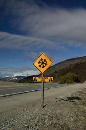 Blazing yellow road sign in the Andes.  Stock Photo - 2874934