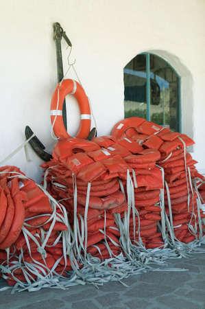 jacked: Stacked blazing orange life jacked with anchor.