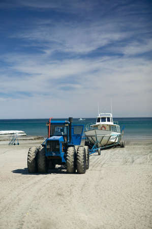 A tractor pulling whale watching ship out of the Atlantic ocean at Puerto Piramides, Argentina. photo