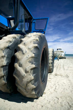 Close-up of a double wheeled tractor, parked on the beach after pulling a Whale Watching boat out of the Atlantic ocean. photo