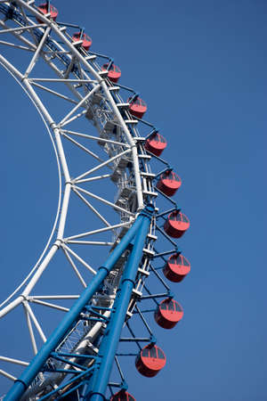 cloudless: Traditional Ferris Wheel with small red cabins in an Amusement Park in TokyoJapan. Stock Photo