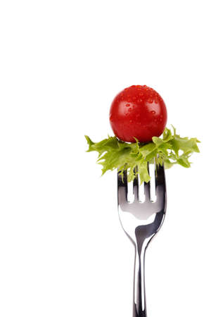 Shiny fork with green salad leaf and red cherry tomato