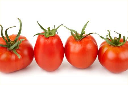 Four fresh and juicy tomatoes standing in a row.
