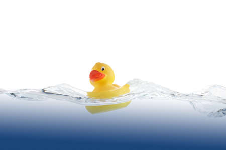 Cute Rubber Duckling swimming in blue undulate water.