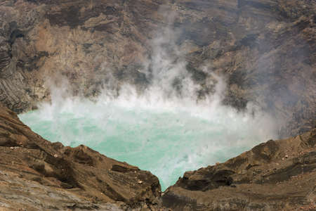 Volcano crater filled up with a phosphorical green steaming lake.