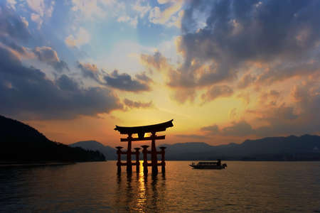 Miyajima Torii silhouette at dusk with cruising boat.  Editorial