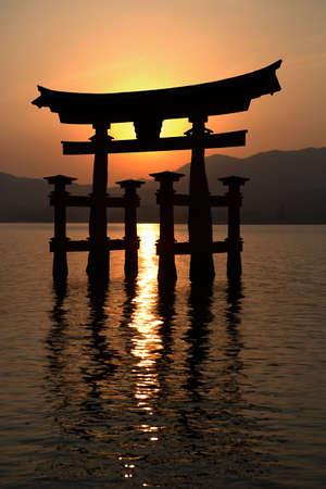 Miyajima gate silhouette at sunset. In the background the mountain range of HirodenmiyahimaguchiHiroshima Prefecture.