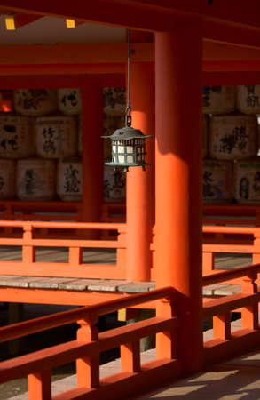 Itsukushima Shrine with traditional lantern at Miyajima, in the background the barrels, depository of sake.