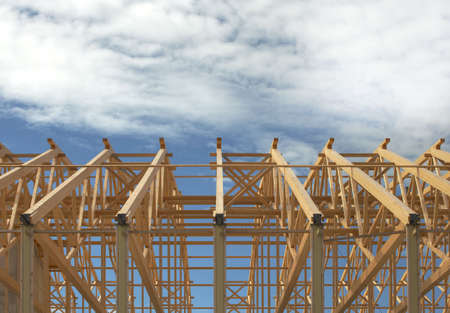 Wooden roof frame on a constructon site over blue sky with clouds.