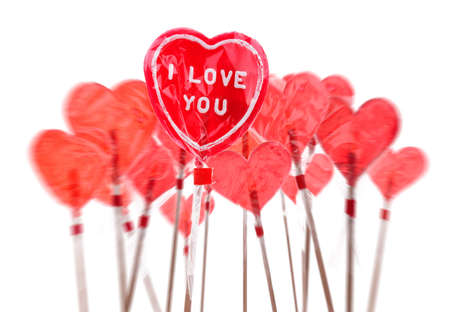 Red heart shaped lollipops over white background. photo
